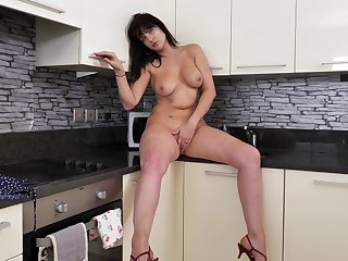 Solo model Jessie drops her dress to sham with her cunt nearby the kitchen